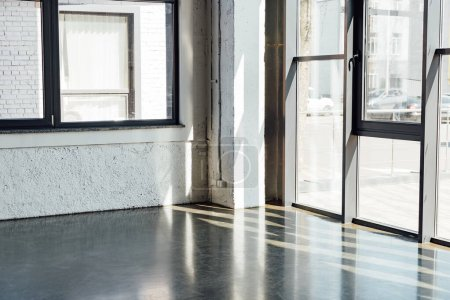 Daylight across windows in sports center with grey floor