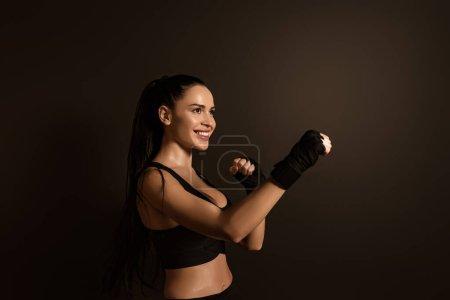 Photo pour Sportswoman souriant et debout en position de combat isolé sur noir - image libre de droit
