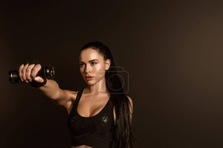 Photo for Brunette sportswoman holding dumbbell with outstretched hand isolated on black - Royalty Free Image