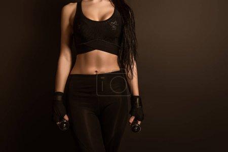 Vista recortada de la deportista en ropa deportiva y guantes deportivos con mancuernas aisladas en negro
