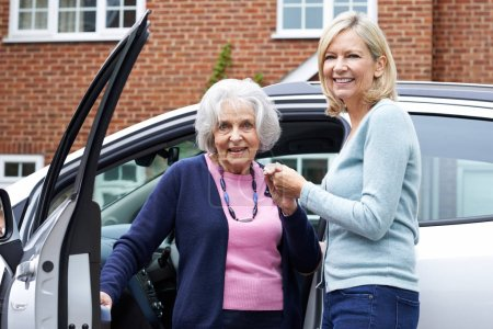 Female Neighbor Giving Senior Woman A Lift In Car...