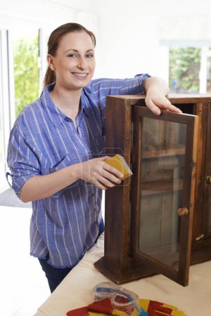 Portrait Of Woman Upcycling Wooden Cabinet At Home
