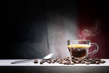 Photo for Steaming espresso coffee in glass cup with coffee bens in dark setting. - Royalty Free Image