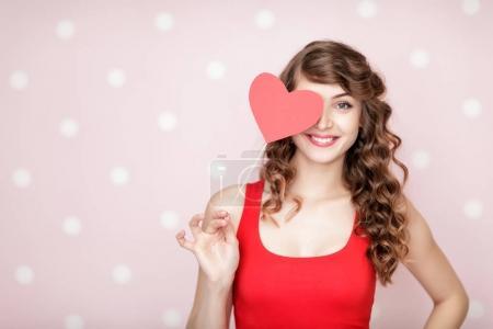 Photo pour Sourire belle femme bouclée tenant coeur rouge sur fond roseavec de l'espace de copie. Saint-Valentin . - image libre de droit