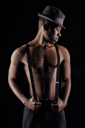 Photo for Afro-american man topless in hat and suspenders on black background. - Royalty Free Image
