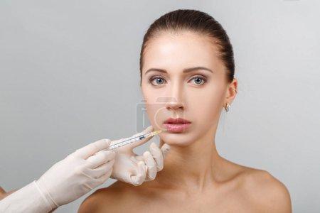 Photo pour Portrait de jeune belle femme obtenant l'injection cosmétique de levage dans les lèvres. Chirurgie plastique. Traitement cosmétique - image libre de droit