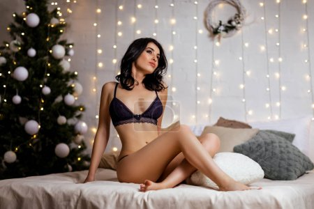 Photo for Sensual sexy woman in erotic black lace lingerie indoors with Christmas tree. - Royalty Free Image