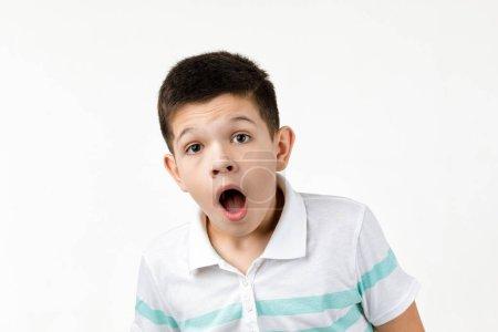 Photo pour Surprise petit garçon en t-shirt regardant la caméra sur fond blanc. Émotions humaines et expression du visage - image libre de droit