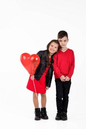Photo pour Des enfants heureux avec un ballon rouge isolé sur fond blanc. Saint-Valentin - image libre de droit