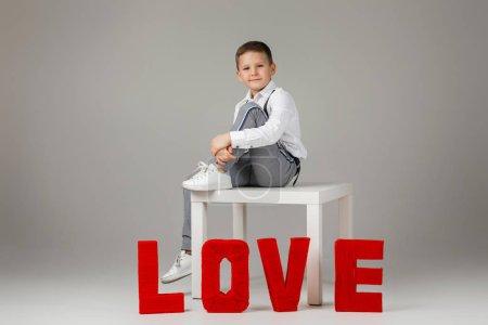 Photo pour Saint Valentin. élégant garçon enfant assis près de lettres rouges LOVE mot sur fond de studio gris . - image libre de droit