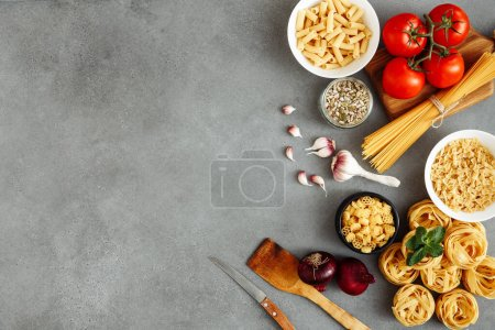 Spaghetti and fettuccine with ingredients for cooking pasta on wooden table with blank of wooden kitchen board, top view. Rustic style. Flat lay with empty space