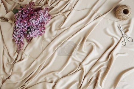 Photo pour Bouquet de lilas, ciseaux et ficelle violets sur tissu satiné de soie. Préparation du bouquet de printemps. Vue de dessus. atlas du printemps avec espace de copie - image libre de droit