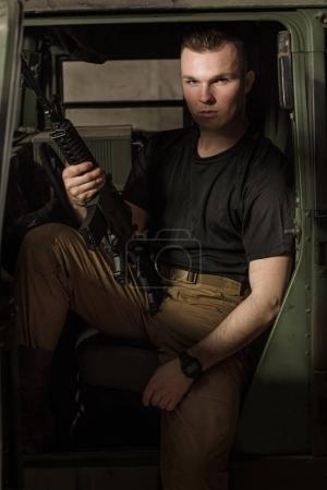 Men in black T-shirt holding gun.