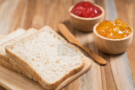 sliced bread with jam on wooden table