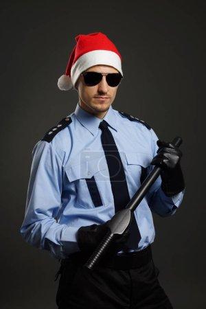 Photo pour Jeune policier comme le père Noël sur fond gris - image libre de droit