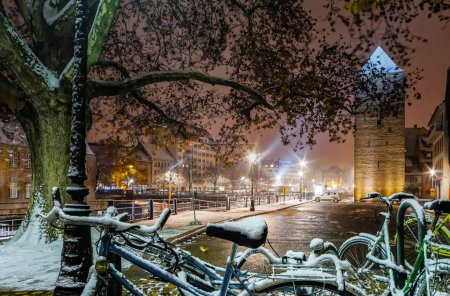 Snow-covered bicycles on the street, Strasbourg, night view, Chr