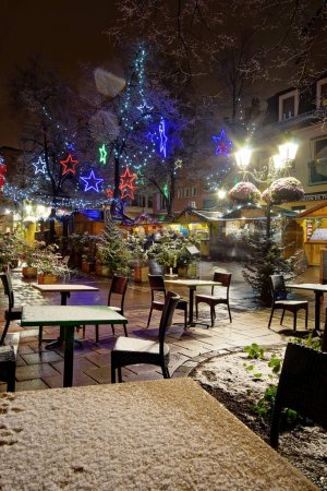 Snow-covered street cafe tables on winter street, Strasbourg, Ch