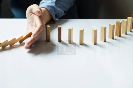 businessman hand stop dominoes