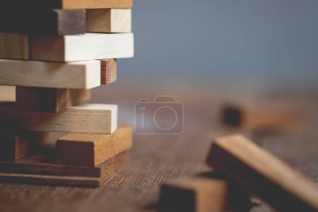Photo for Blank wooden blocks leaning on a structure made of many other blocks with several of them still lying scattered on a textured rustic wooden desk. Conceptual of leisure game or start up business concept - Royalty Free Image