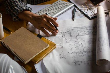 kreativer Architekt, der im Dunkeln auf die großen Zeichnungen projiziert