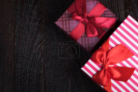 One gift box with an red big ribbon on old wooden dark brown bac