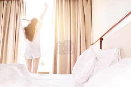 Healthy Woman stretching in bed room and open the curtains after