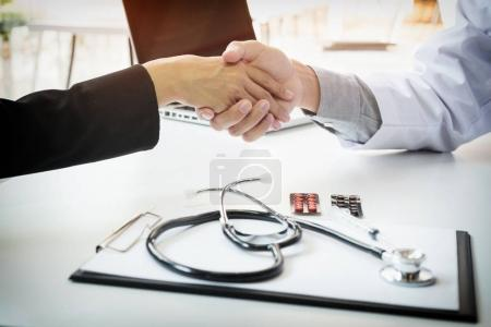 Male doctor in white coat shaking hand to female colleague
