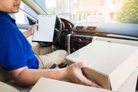 Delivery man with cardboard box checking document list In van an