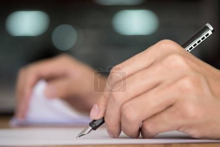 Businessman writing in a document. Focus on the tip of the pen