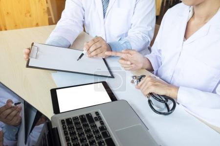 Two doctors discussing patient notes in an office pointing to a