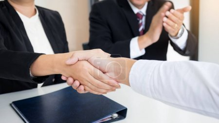 successful business team shaking hands with eachother in the off