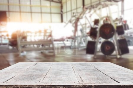 Wooden table on blurred background of fitness gym interior of mo