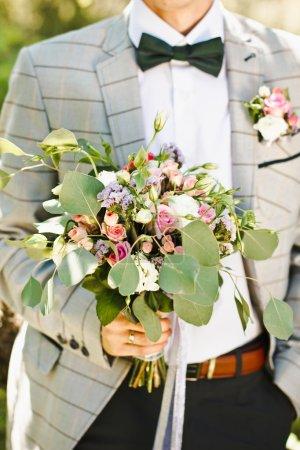 Groom hold beautiful wedding bouquet
