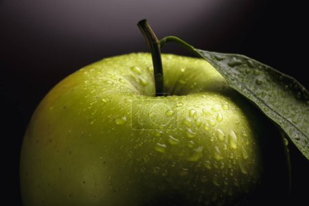 Large beautiful green apple with a leaf and water drops