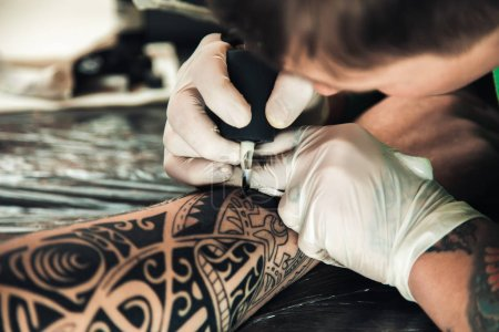 Master tattoo artist in gloves makes tattoo on hand men