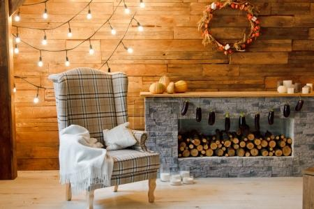 Armchair near the fireplace with firewood