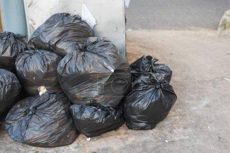 Bild einer schwarzen Mülltüte auf der Straße.