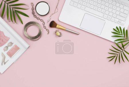 Photo pour Concept d'achat en ligne avec ordinateur, fond rose, catalogue et produits - image libre de droit