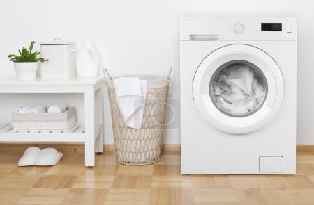 Laundry room interior with washing machine, basket and white shelves