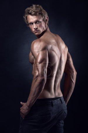 Photo pour Modèle de fitness homme athlétique fort posant les muscles du dos, triceps, latissimus - image libre de droit