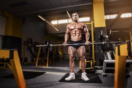 Muscular bodybuilder guy doing exercises with dumbbell