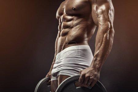 Muscular bodybuilder guy doing exercises with dumbbell disc