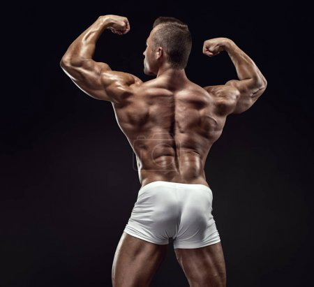 Strong Athletic Man Fitness Model posing back muscles, triceps