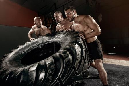 crosss trongman training - three men flipping tire