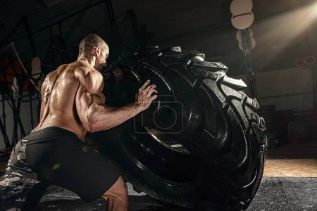 Photo for Muscle cross strongman training - man flipping big tire - Royalty Free Image