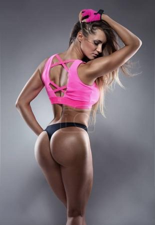 Nice sexy fitness woman showing buttocks, back posing