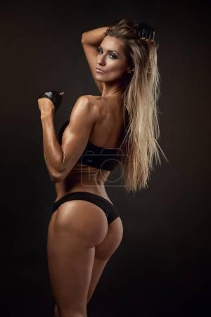 Photo for Nice sexy fitness woman showing buttocks, back posing, retouched isolated over grey background - Royalty Free Image