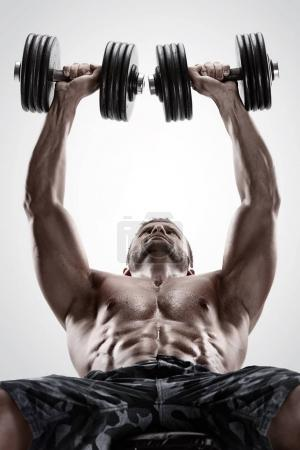 Muscular bodybuilder guy doing exercises