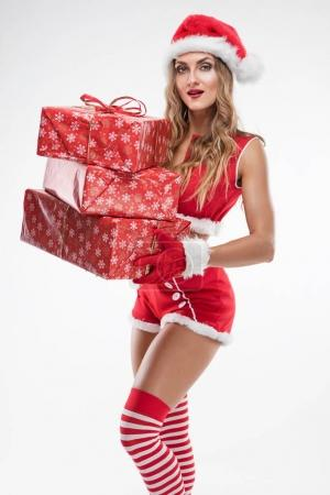 Photo for Beautiful sexy girl with gifts wearing santa claus clothes over white background - Royalty Free Image