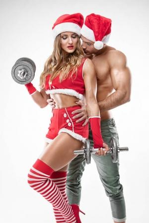 beautiful sexy couple in santa claus clothes doing workout